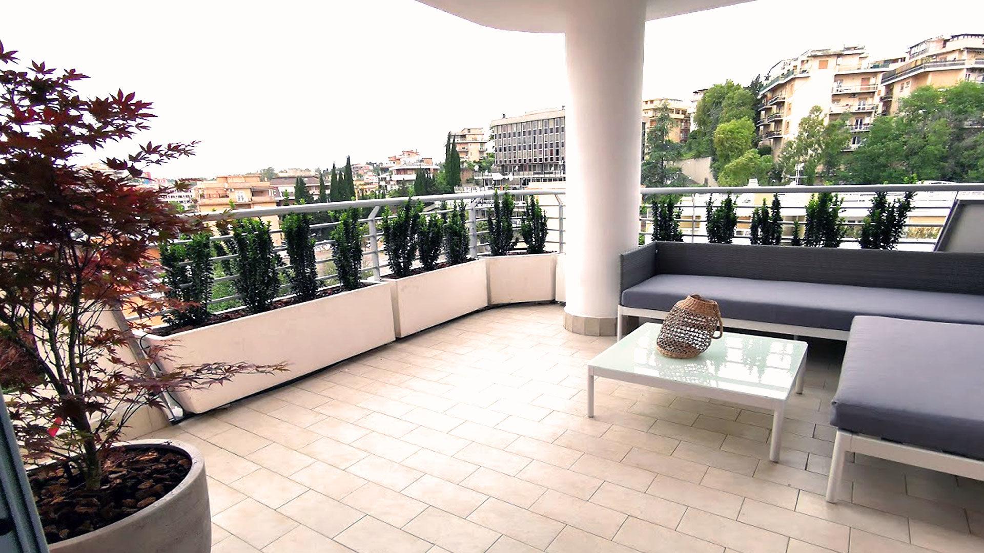 Terrazzo di design arredato con piante, divano e tavolino. Daniele Proietti e Salvatore Gagliano. Siamo presenti a Roma e Milano. Ornus.